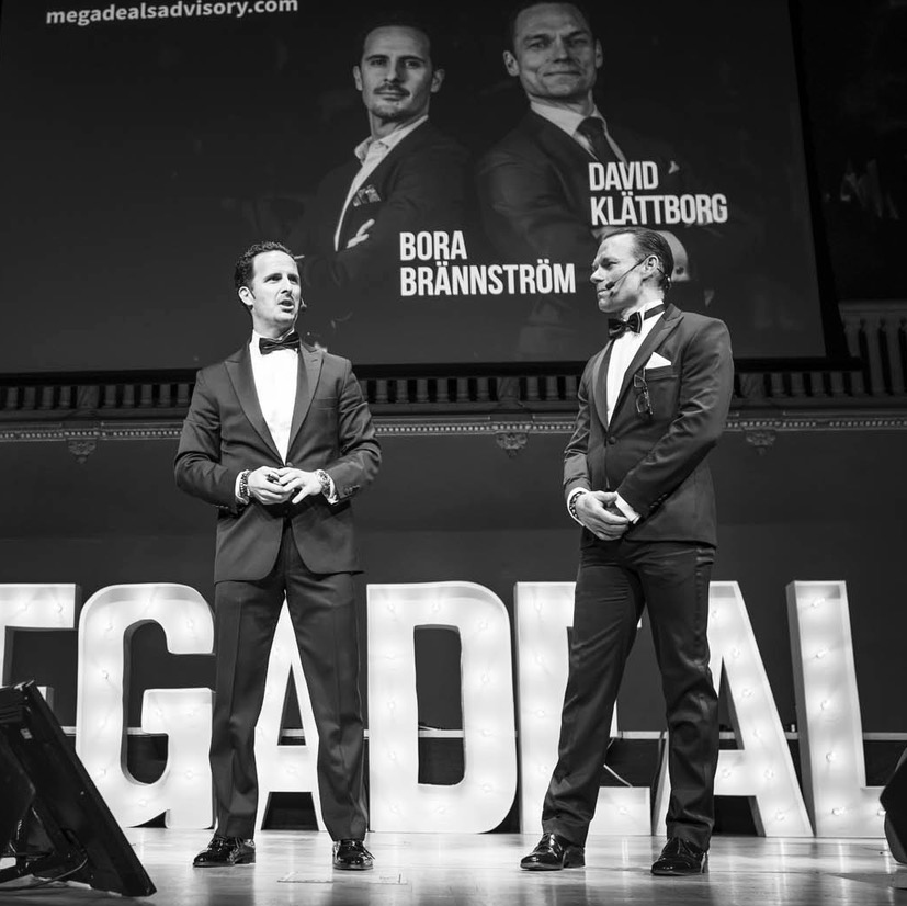 Picture of two co-founders of megadeals gving a presentation