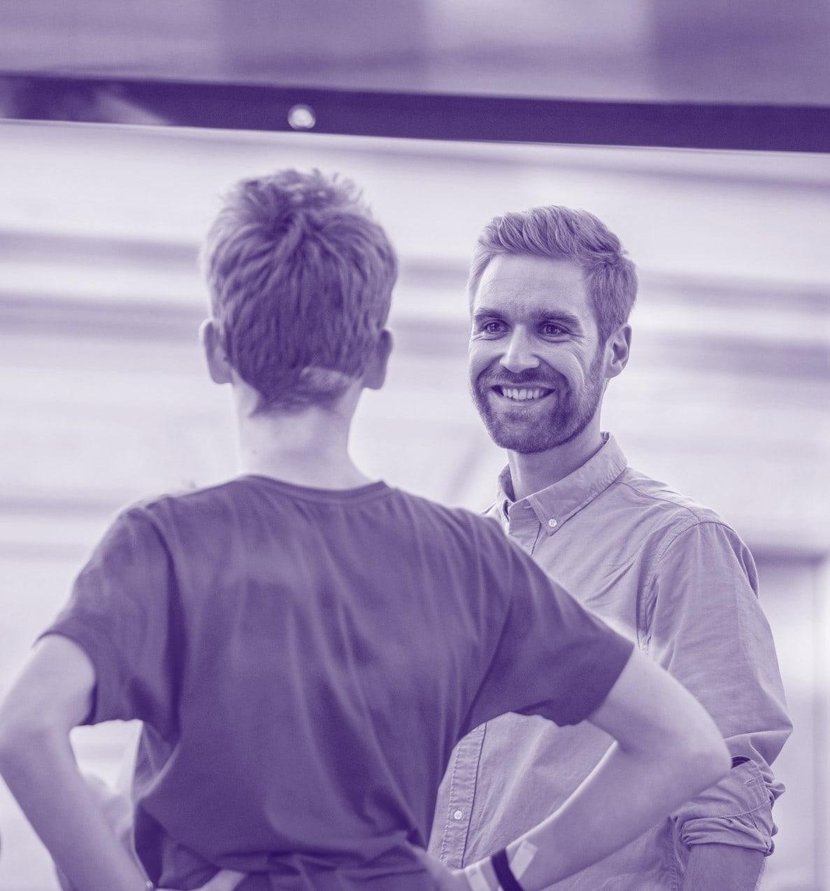 Zwei Männer, einander zugewandt einer lächelt.