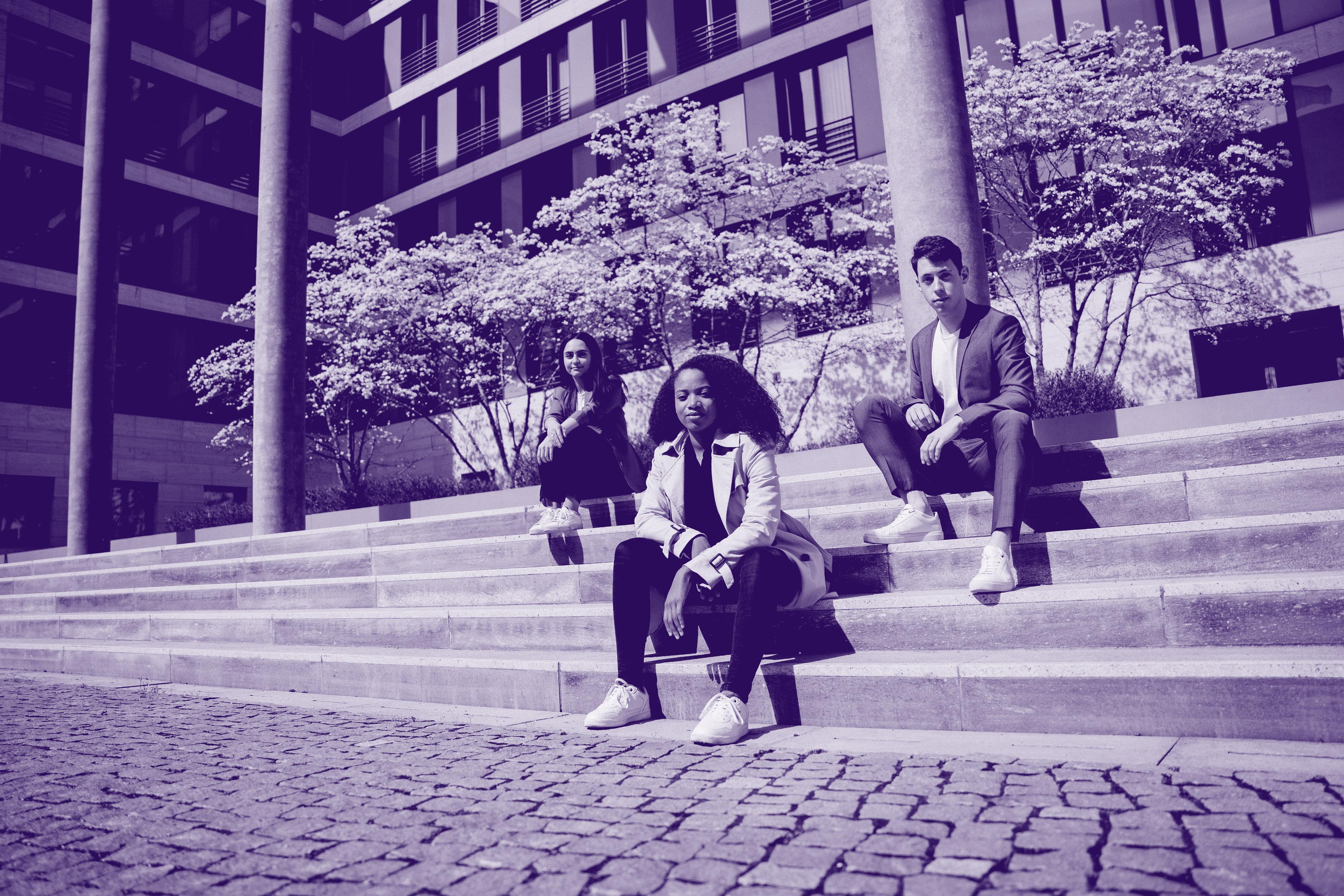 Drei junge Menschen sitzen auf Treppenstufen