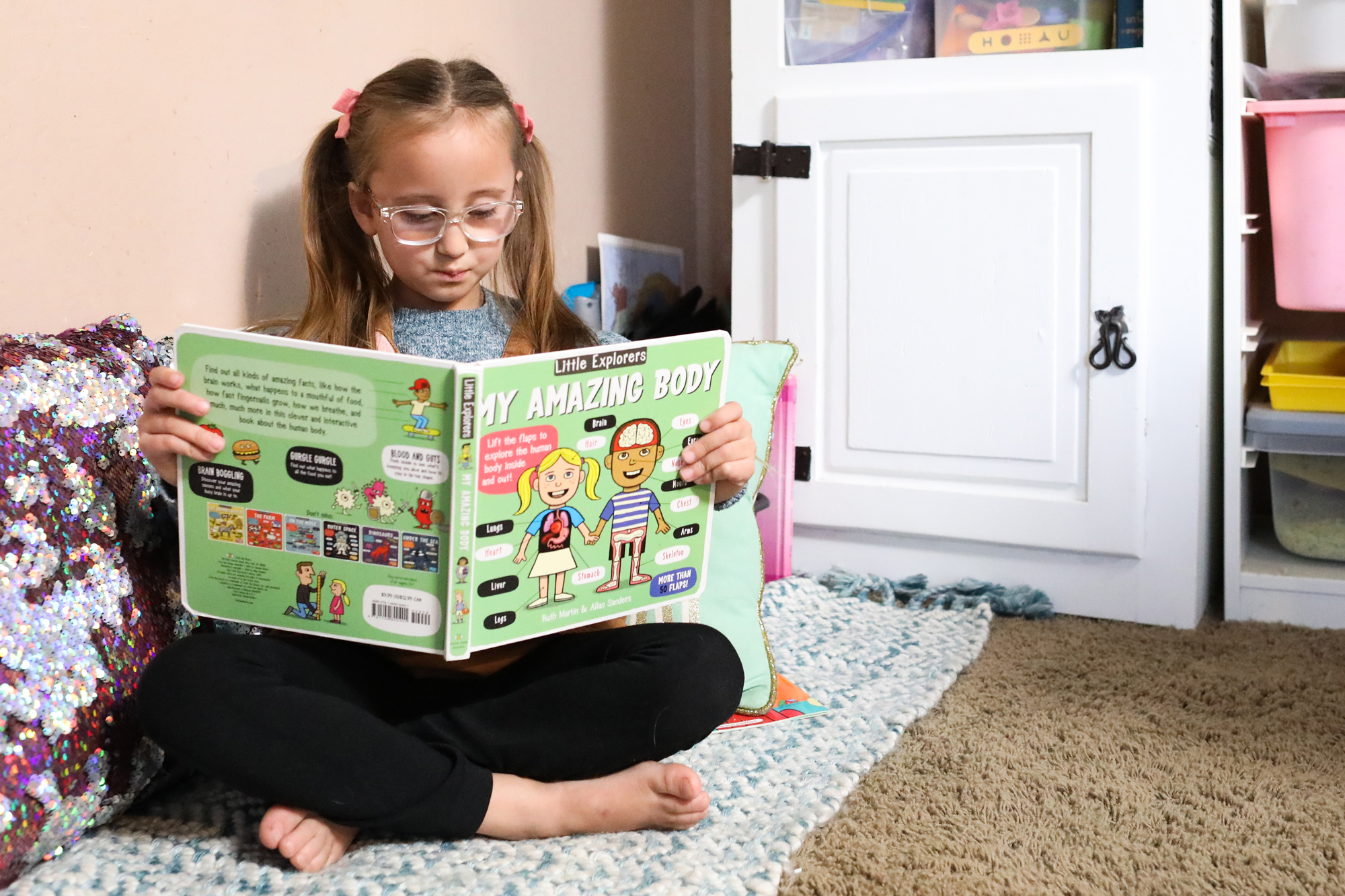 Elementary age girl reading a picture book at home