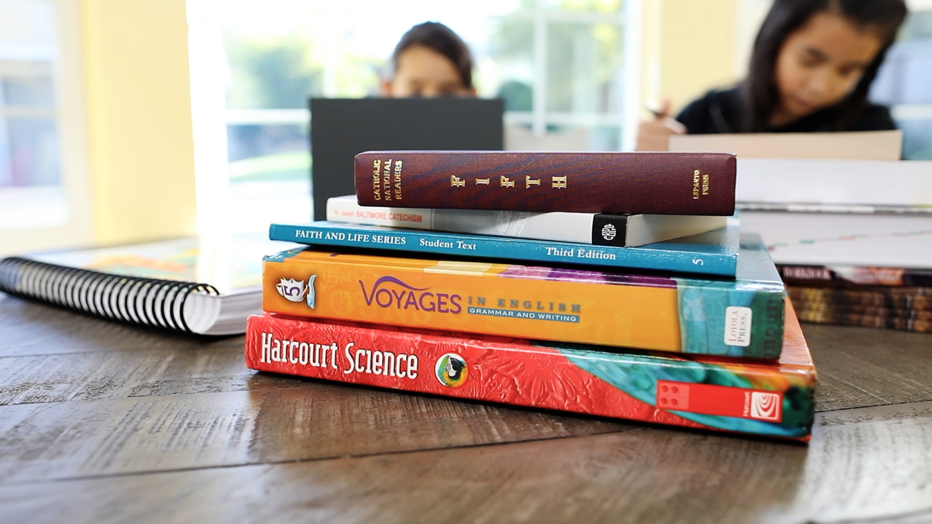 Small stack of textbooks on a table with two children studying in the background