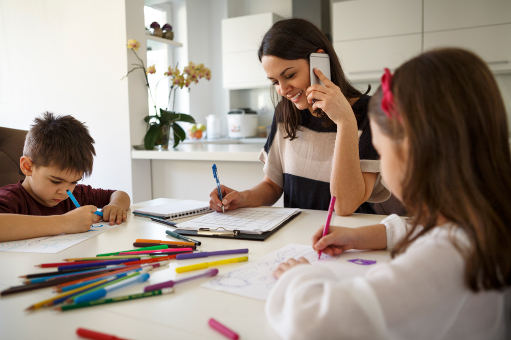 Young mother takes notes while making a phone call and her daughter colors a picture