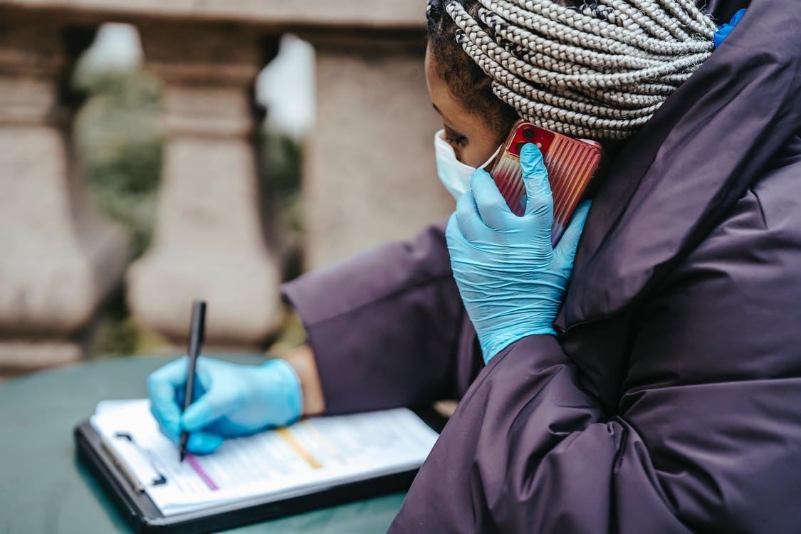 Femmes avec des gants médicaux ayant une conversation téléphonique et qui note sur papier.