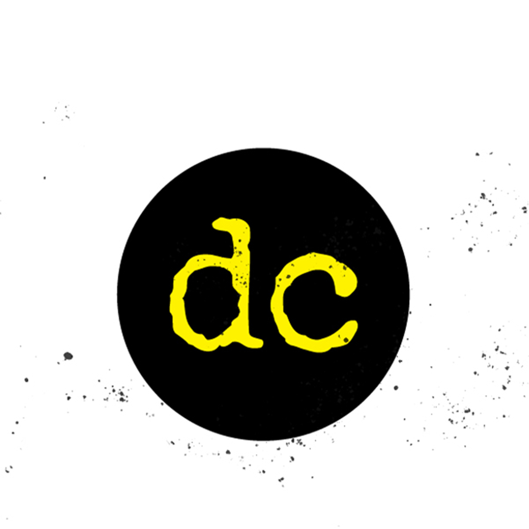 A black circle logo with dc in yellow typewriter font. The logo is distressed with ink splatter on and around it.