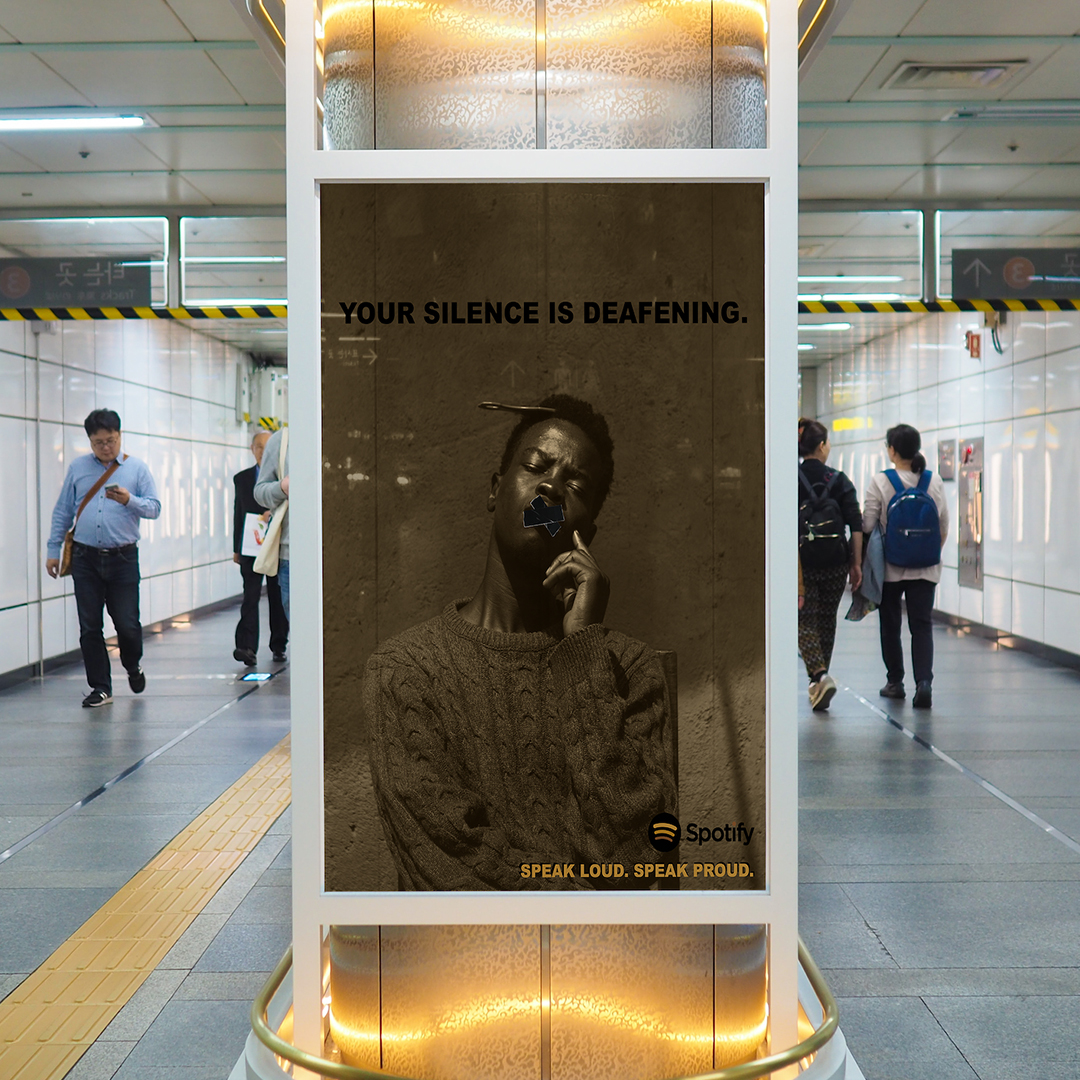 """A transit ad in an underground subway passage. The ad is a duotone in black and yellow of an African American with tape over his mouth. His eyes are closed. At bottome right the text reads """"Spotify"""" """"Speak Loud. Speak Proud."""""""