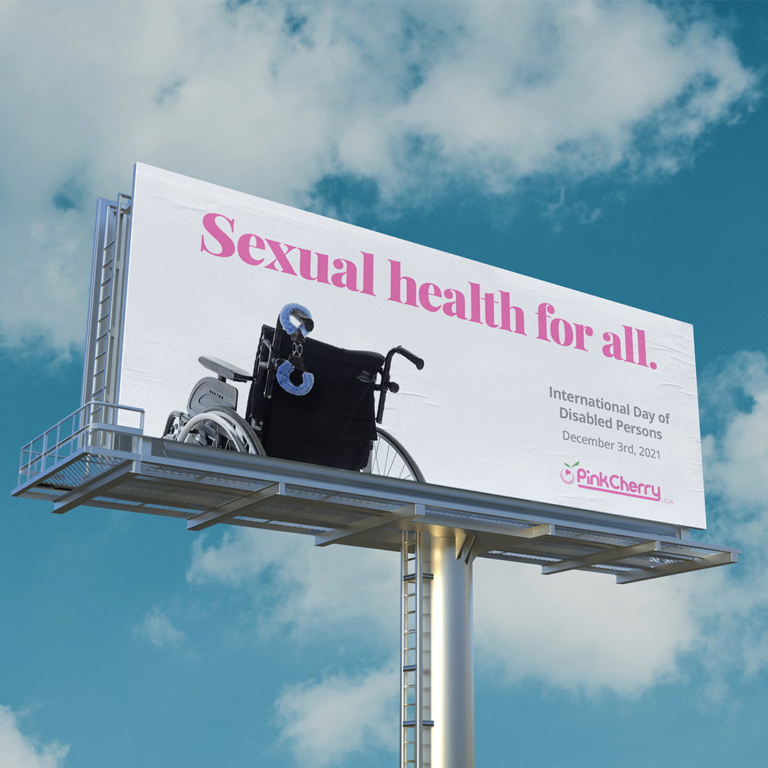 """A billboard agains a blue sky. The all white background with large pinnk type that reads """"Sexual health for all."""" A wheelchair is cropped off the bottom left of the billboard with type on the right that reads """"Internatioanal Day of Disabled Persons"""" and the Pink Cherry logo at bottom of billboard."""