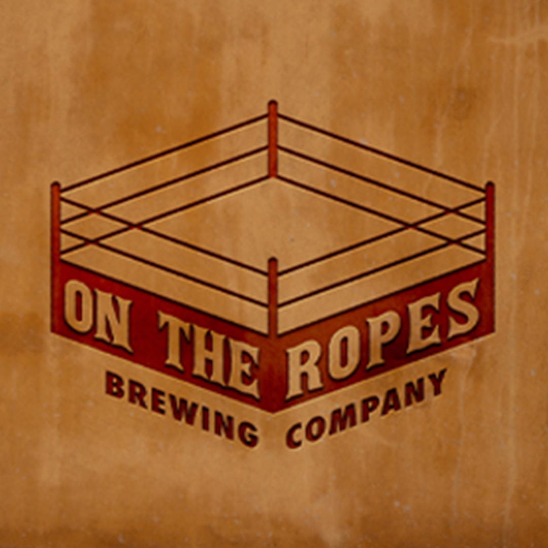 """A logo for a brewing company. There is a drawing in red of a boxing ring and underneath the name """"On the Ropes Brewing Company.""""  The logo is placed on a distrssed brown background."""
