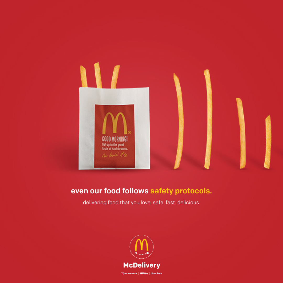 """A McDonalds ad shows a red background with french-fries lining up to jump into the package but keeping social distance measures between them. The fries approach the package on the left from the rigth side of the ad. The copy reads """"even our food follows protocals"""" """"delivery food that you love. safe. fast. delicious."""" The logo appears at the bottom centre of the ad."""