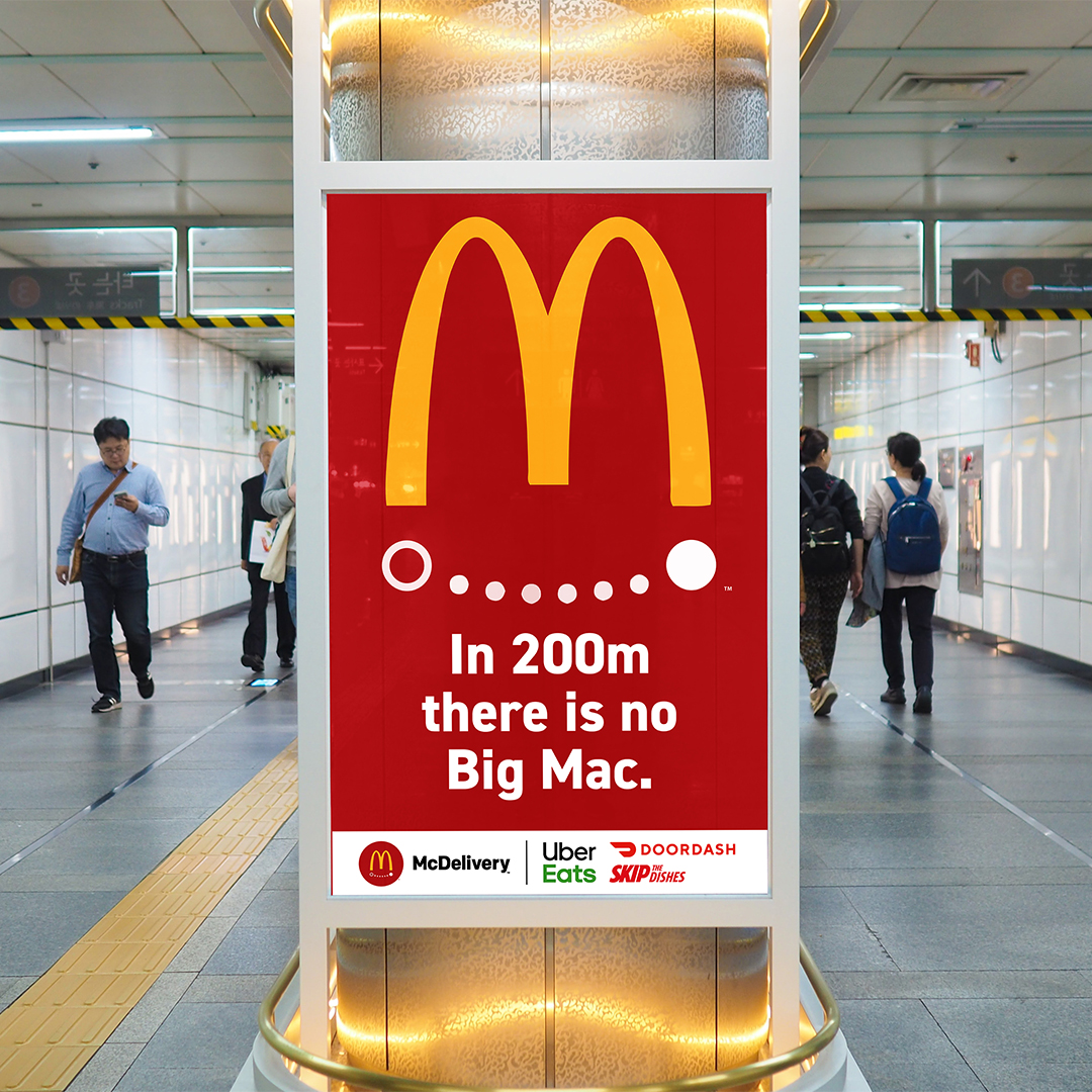 """A subway poster advertisement for McDonalds. A red background with the Golden Arches drawn. Underneath are with dots that form a smile. The text underneath says """"In 200m there is no big mac."""""""