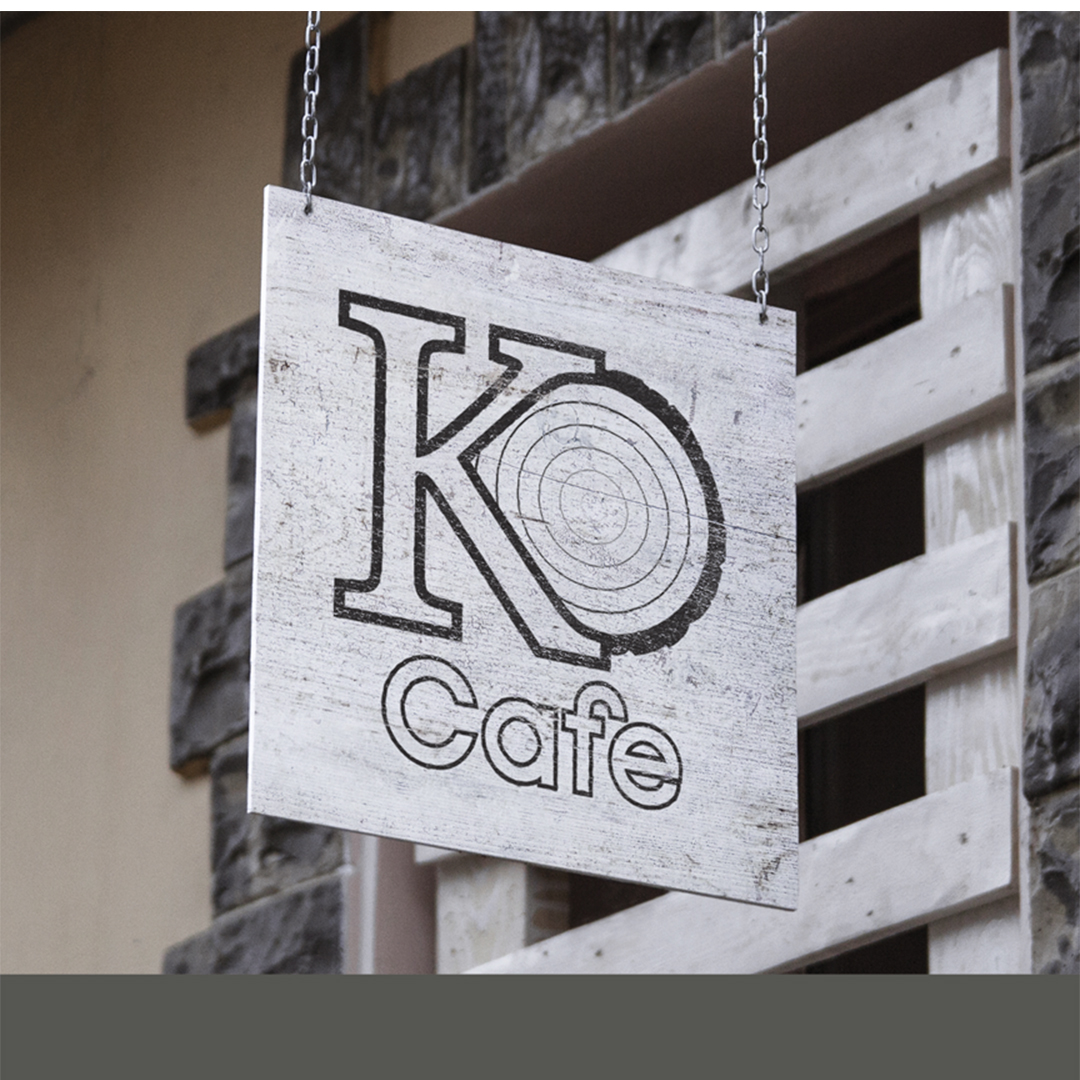 """A white and black logo hangs on wooden storefront sign the logo reads """"KO café"""" in black cut out letters. The """"O"""" is drawn like a cross section of a tree trunk."""