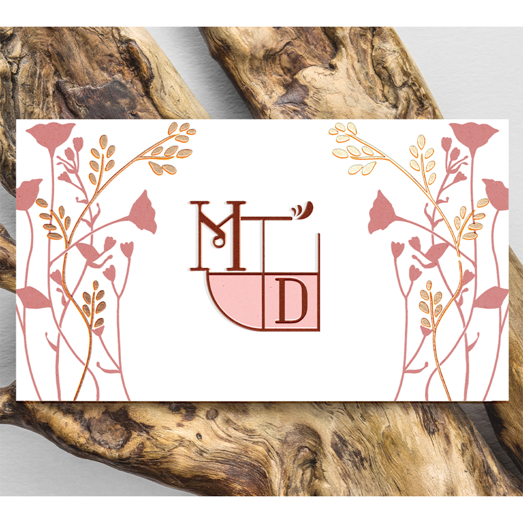 A logo with the Inistials MD in maroon on a pink shape. Pink and gold flowers one either side. The business card is set on a piece of driftwood