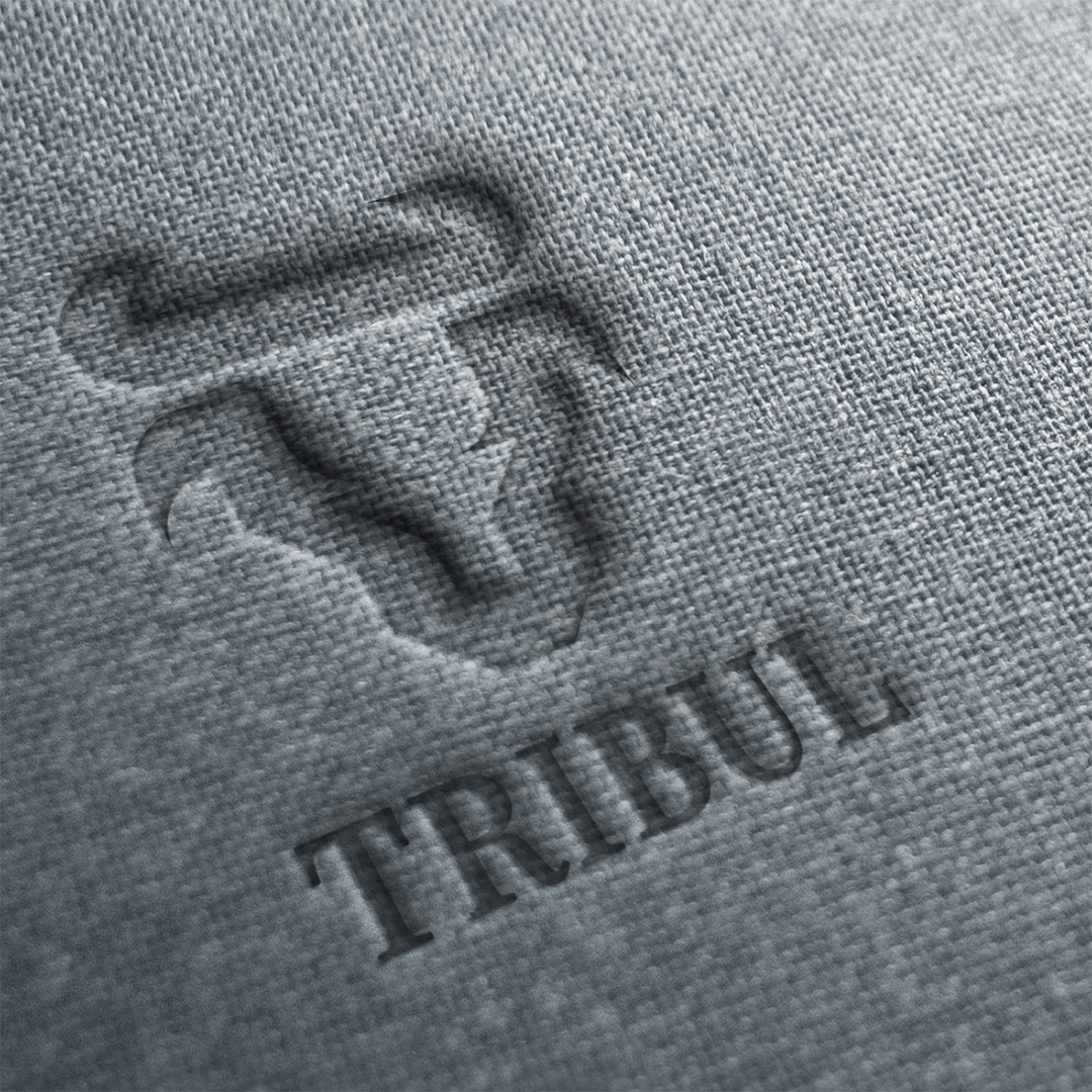 A logo for a company called Tribul with a stylized bullhead with horns imprinted on a rough grey fabric surface.