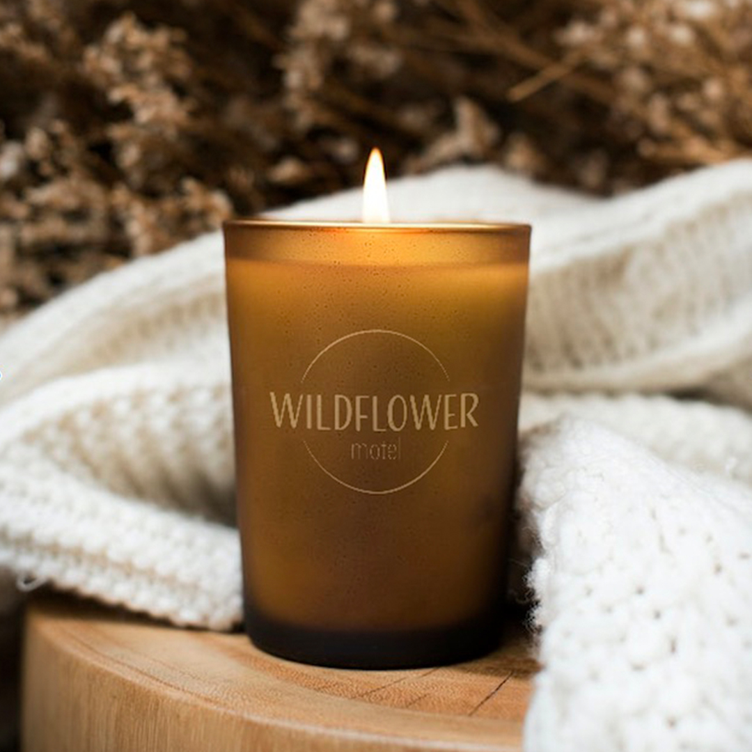 """A photo of the Wildflower Motel logo on a image of a lit brown candle. The logo is gold and set within a circle with the text """"motel"""" set below. The font is sans serif."""