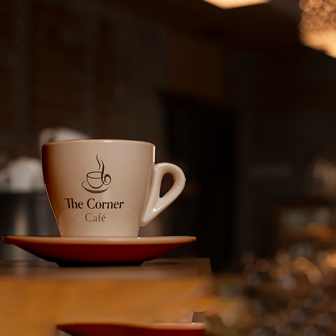 """A coffee cup with the logo """"The Corner Café"""" sits on a wood table."""