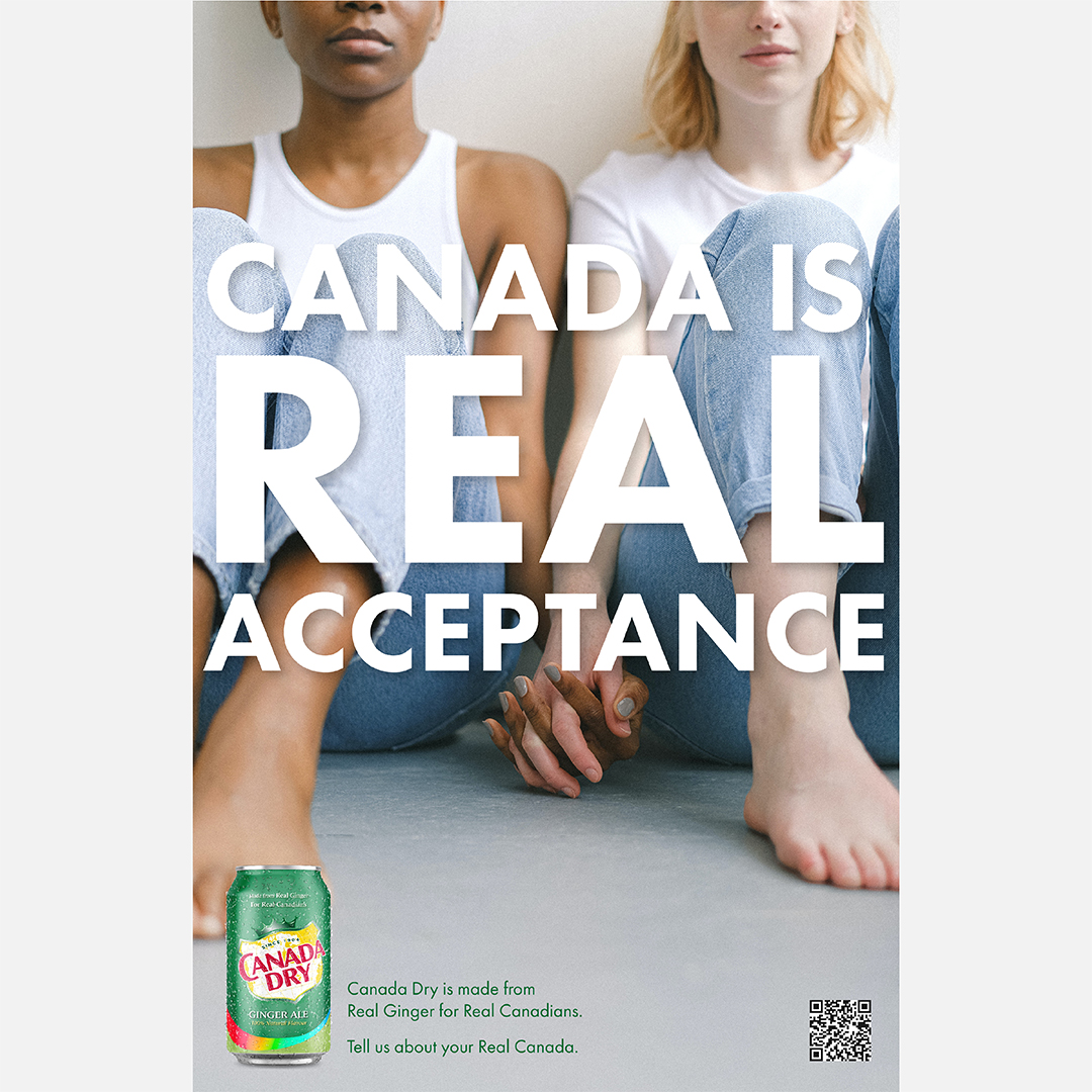 """As Canada Dry Gingerale advertisement showing two women seated, wearing jeans and holding hands. One is of African American decent and one is white. The text that appears in the front of the couple in large white letters reads """"Canada is Real Acceptance."""" Below beside the product shot reads """"Canada Dry is made from real ginger."""""""
