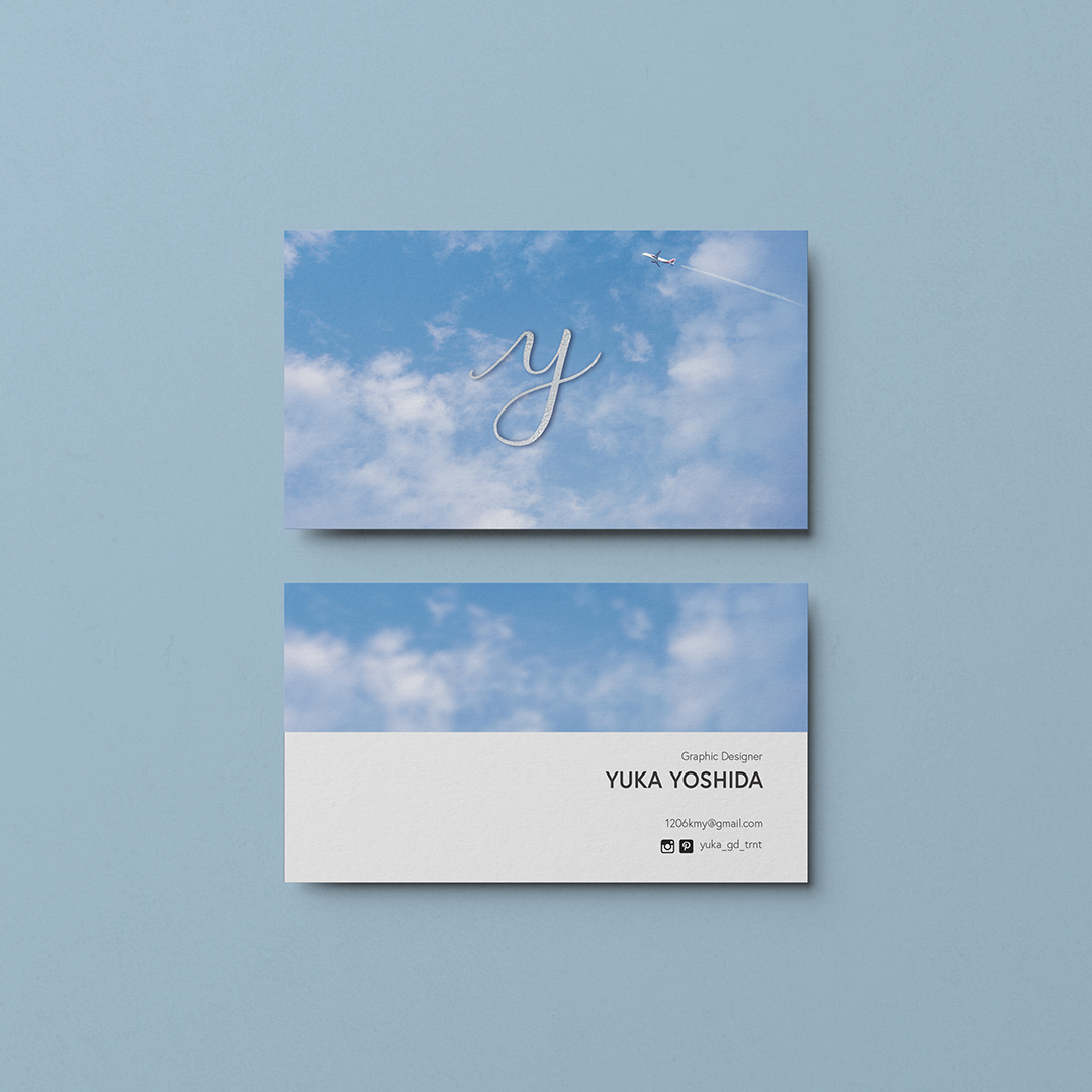A photo of a business card front and back on a blue background. The card front is a blue sky with a y in script letter. There is a small airplane to the upper right corner. The back of the card is the sky again with the artist's name and title. Graphic design Yuka Yoshida.