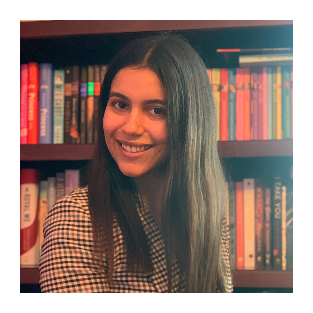 Female identifying person with long brown hair, smiling in front of bookshelf