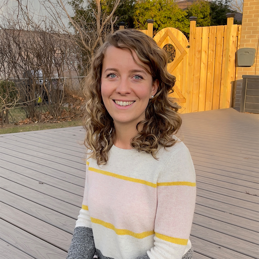 Female identifying person in striped sweater, smiling, outside on a deck