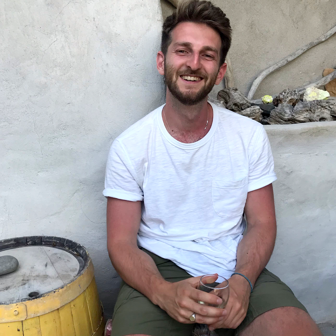 Male identifying person wearing a white t-shirt smiling, outside