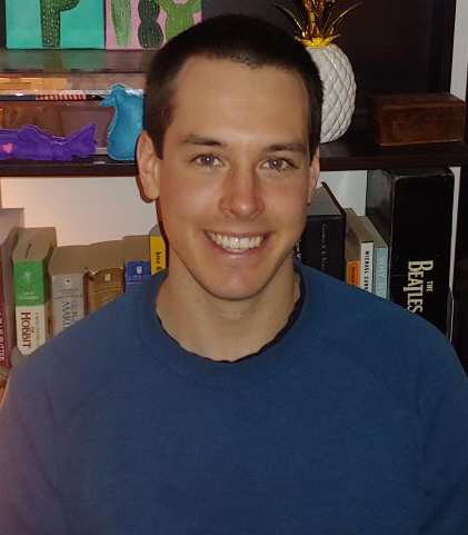 Male identifying person in blue shirt, in front of a bookshelf with a pineapple.