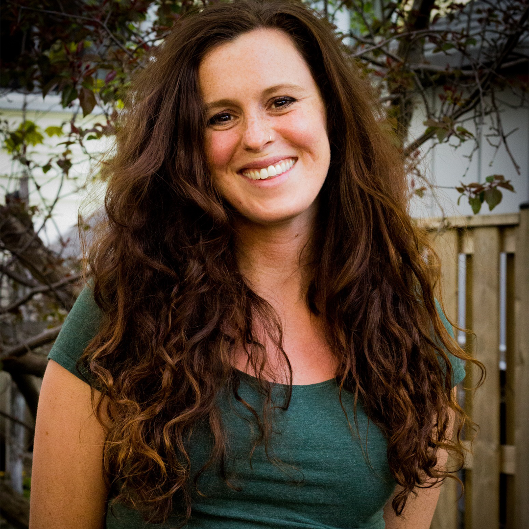 Female identifying person with long brown curly hair, smiling outside