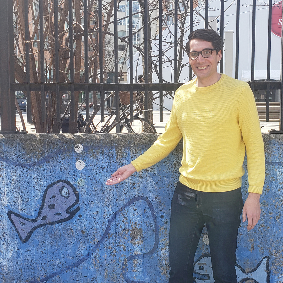 Male identifying person wearing glasses and a yellow shirt, gestures at fish painting, outside