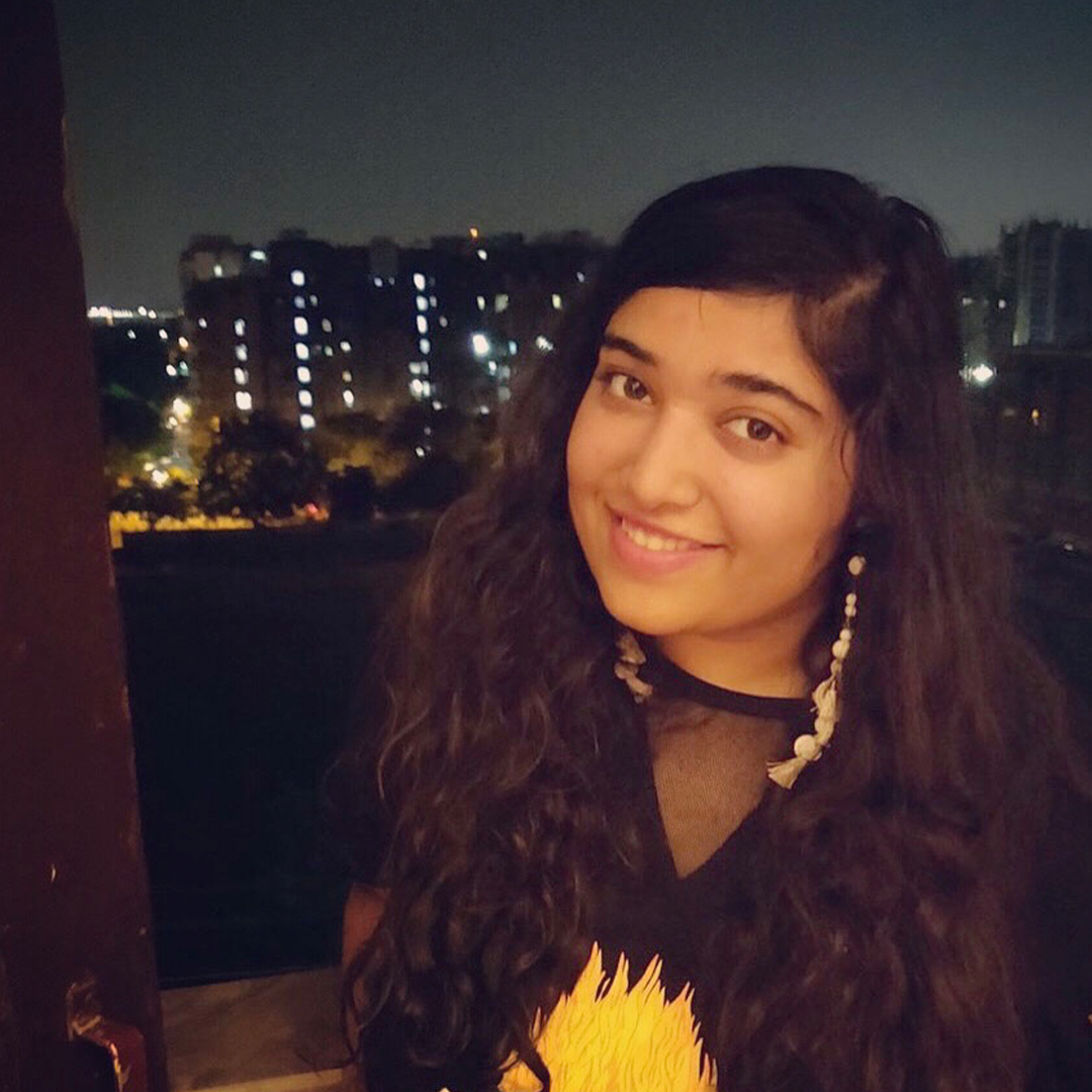 Female identifying person with long brown hair and long earings,  against a night-time city background.