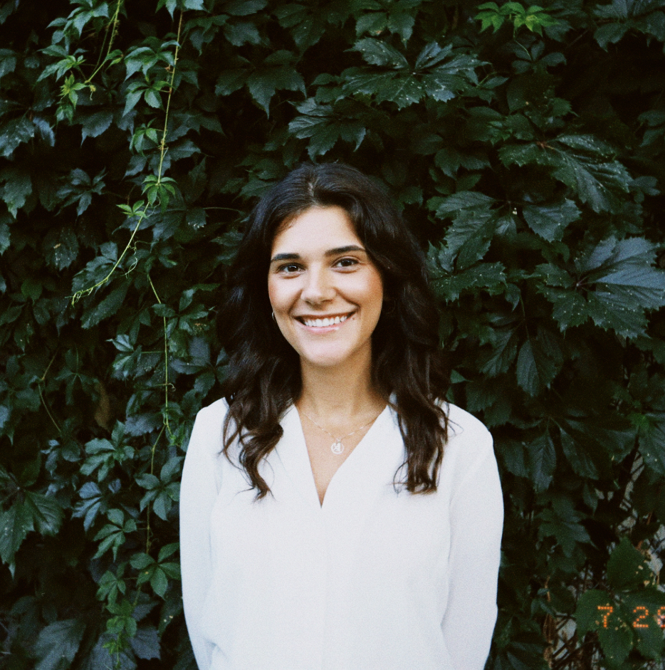 Female identifying person wearing a white shirt smiling outside, in front of a wall of vines.