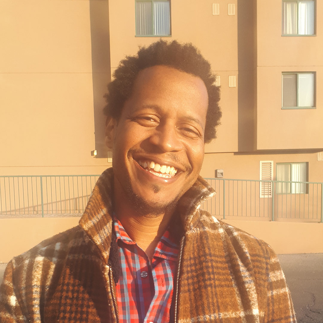 Male identifying person wearing a checked coat, smiling outside, in front of a building