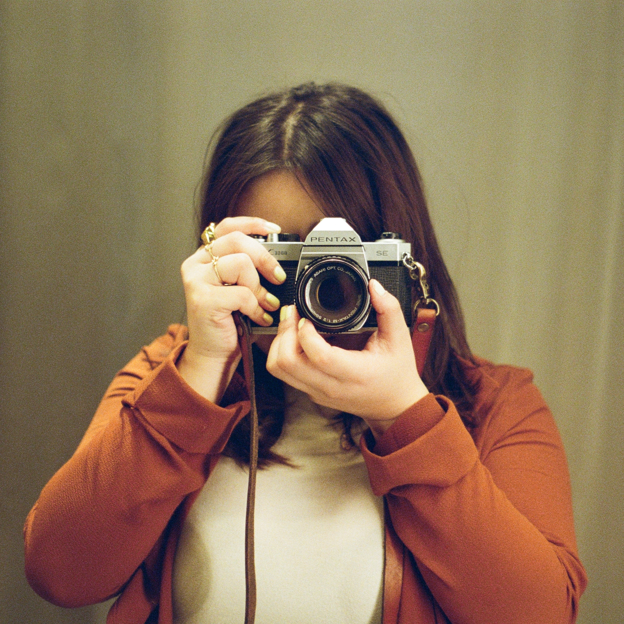 Portrait of Chalista taking a picture with her camera, wearing a red jacket and while blouse