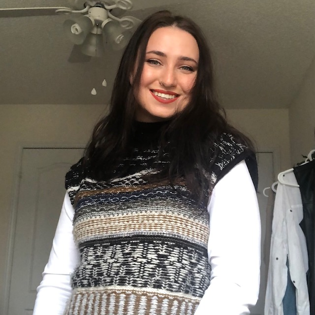 Picture of Jamie, smiling at the camera, wearing a black/brown/white vest with a long sleeve white blouse