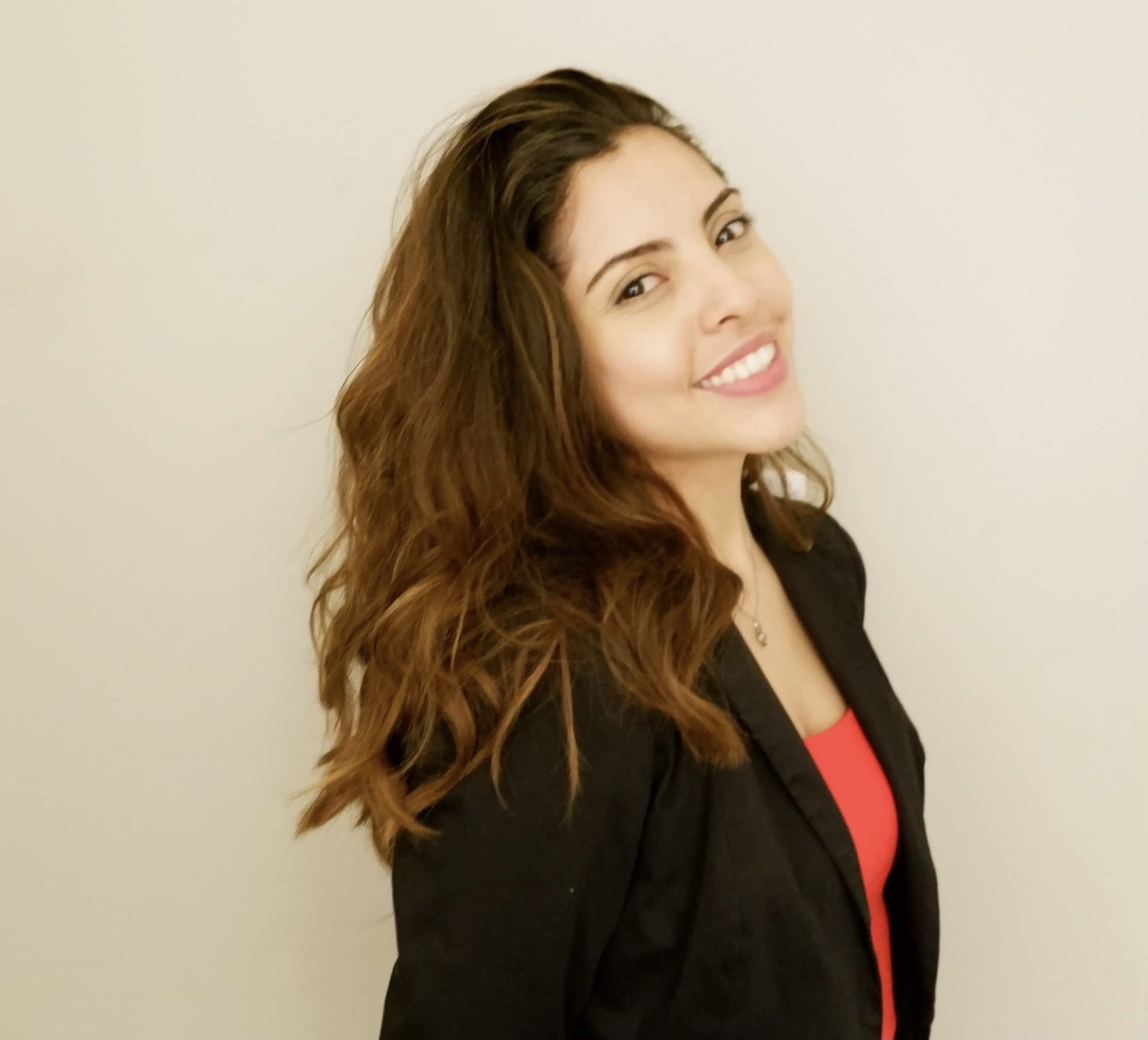 Portrait of Maria, smiling and posing with a black blazer and a red tank top