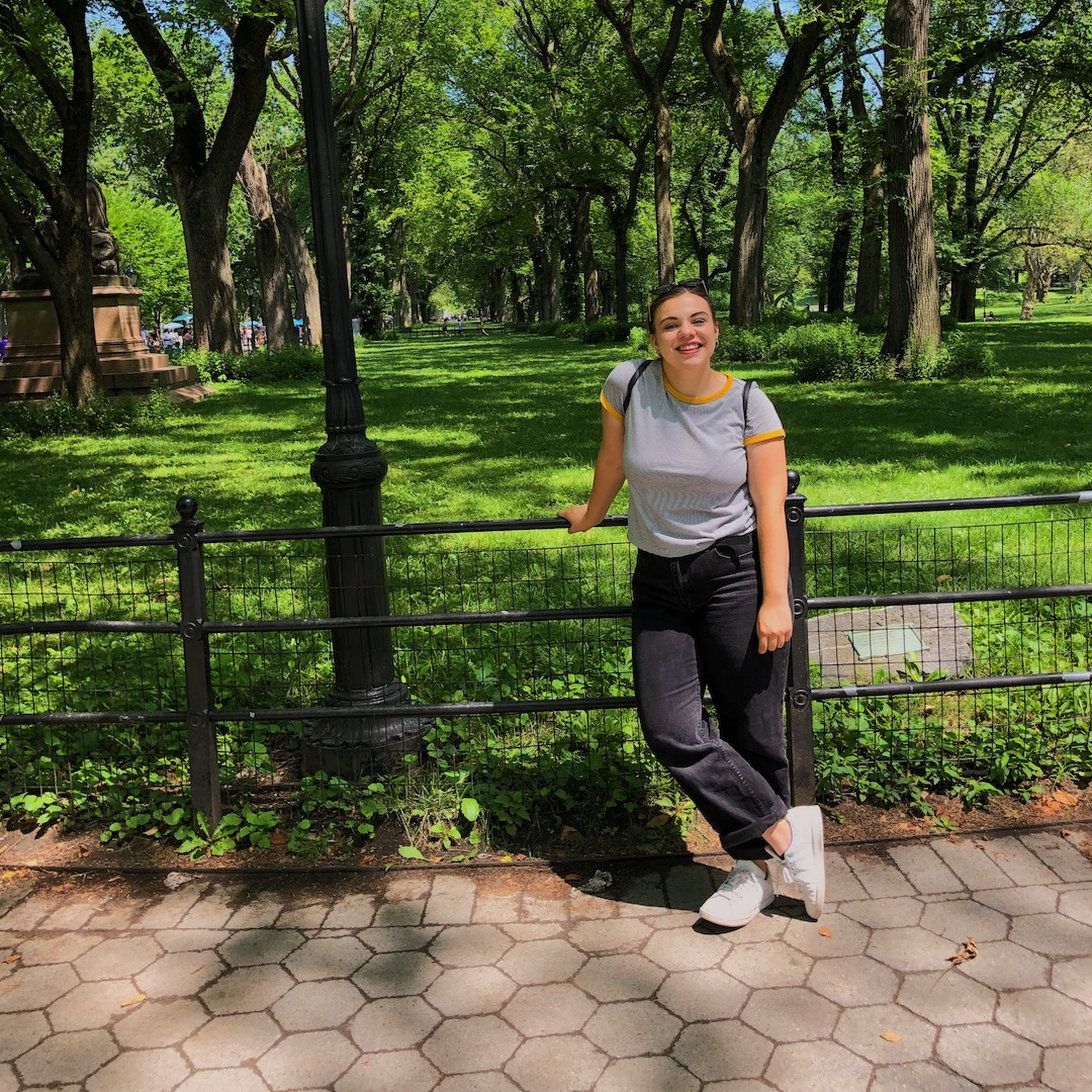 Image of Rachel in a park, leaning on a fence.