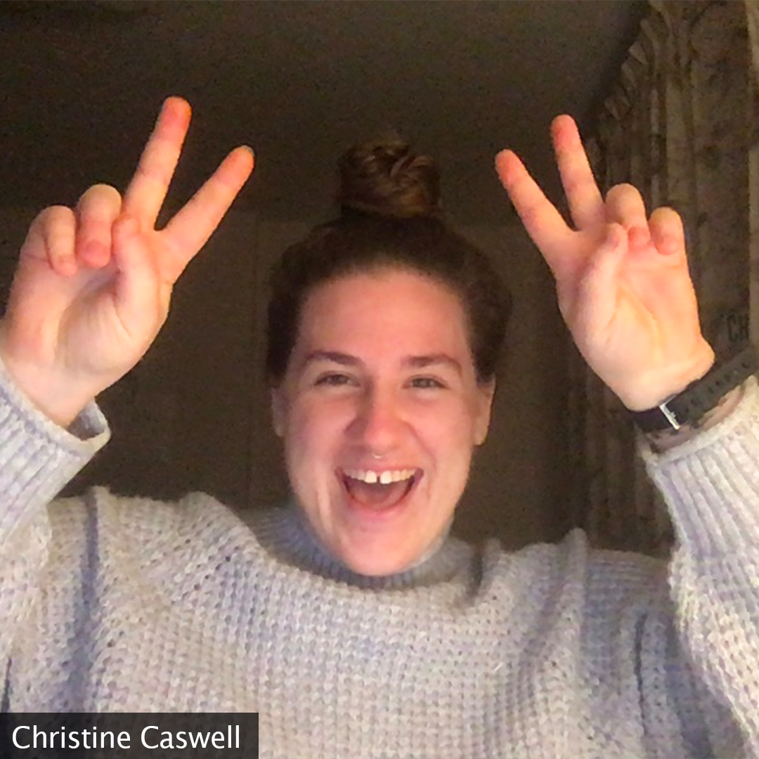 Picture of creator in a light grey turtleneck sweater smiling at the camera and she is throwing up a peace sign on both hands at each side of her.