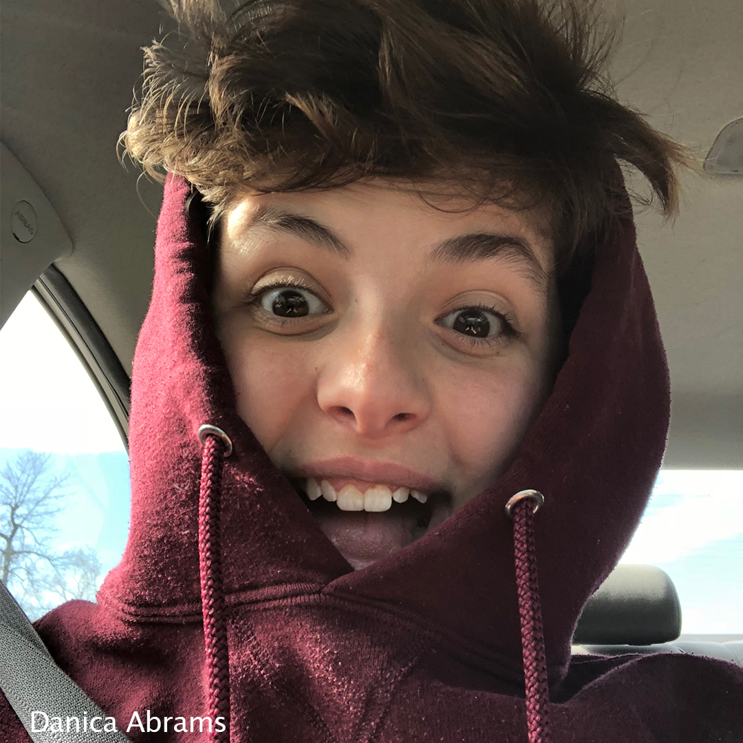 Photo of Danica wearing a hooded sweatshirt with a surprised and happy expression