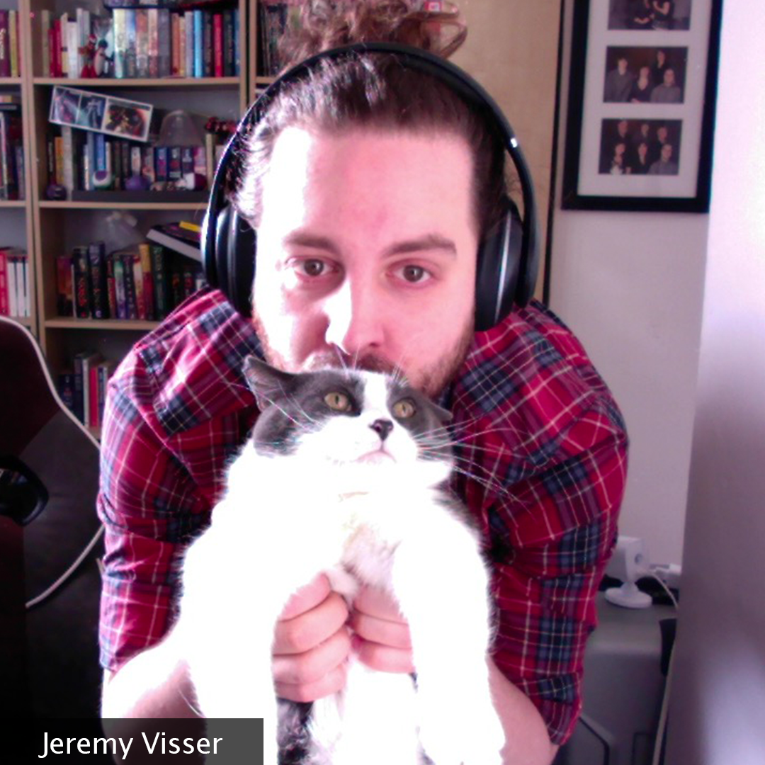 A man with a bun in his home office smooching his cat and partner in crime, Artemis