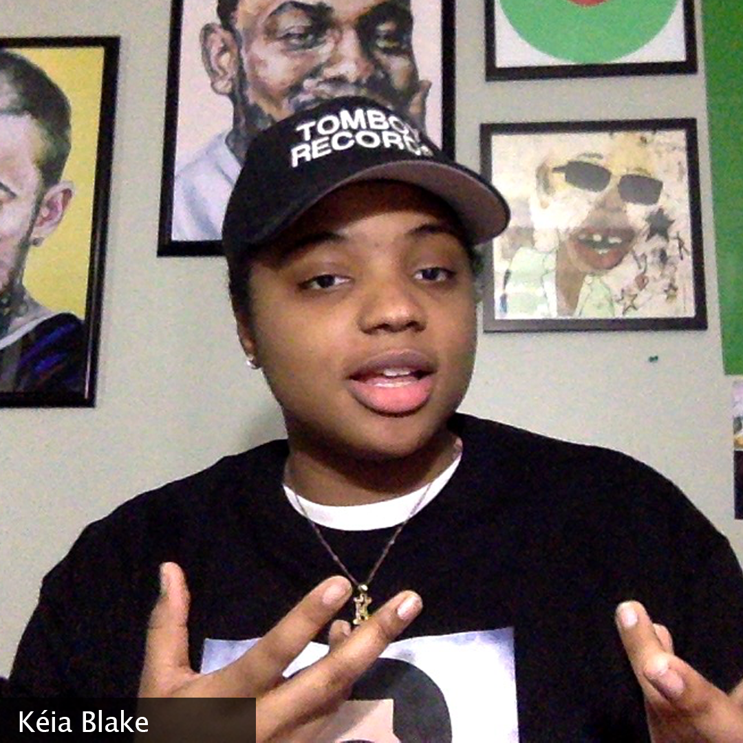 """Photo of Keia mid statement wearing a """"Tomboy Records"""" hat. The wall behind her has posters of several hip hop artists:"""