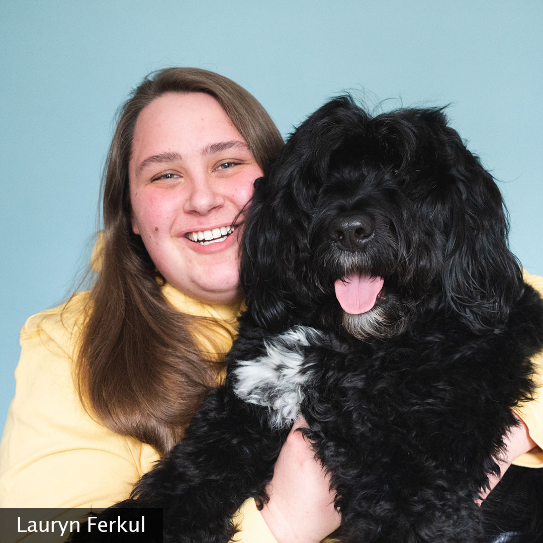 Lauryn is smiling at the camera wearing a yellow hooded sweatshirt and her black, fluffy dog, Olie, is snuggled beside her.