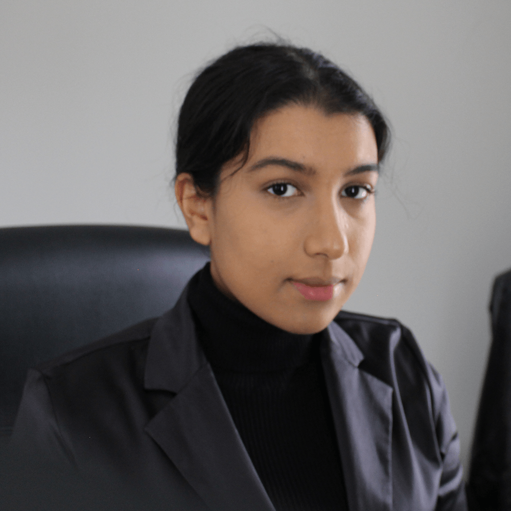 Aisha sitting and looking at the camera wearing a black turtle neck t-shirt with a light-black blazer