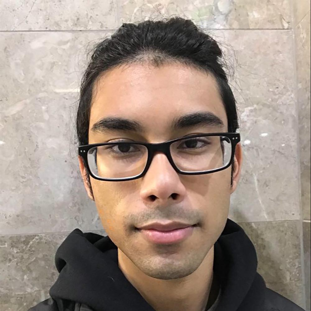 Picture of Alex Sumeer against a wall, wearing glasses and a black hoodie