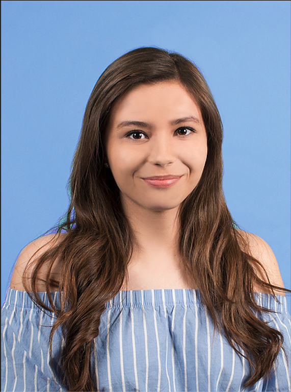 Headshot of Ariana, smiling to the camera and wearing a blue and white shirt