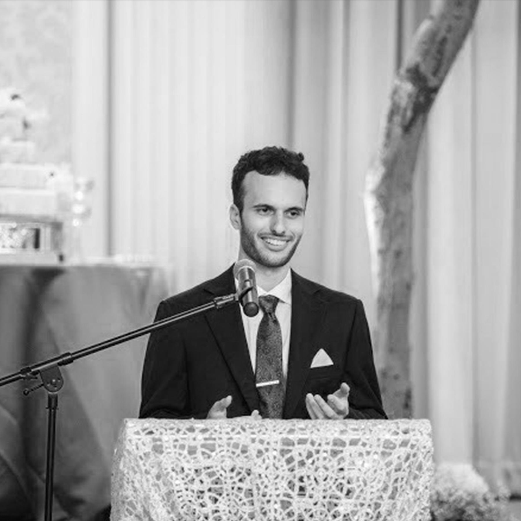 Dusan Mandic wearing a suit giving a speech