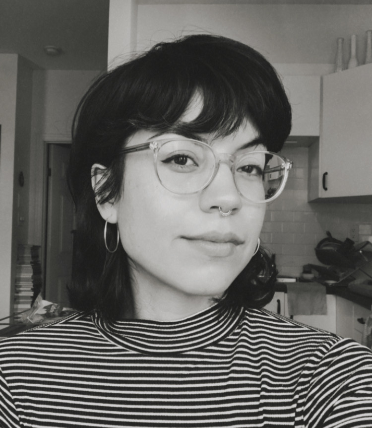 Black and white photo of a woman with short, dark hair, and glasses.