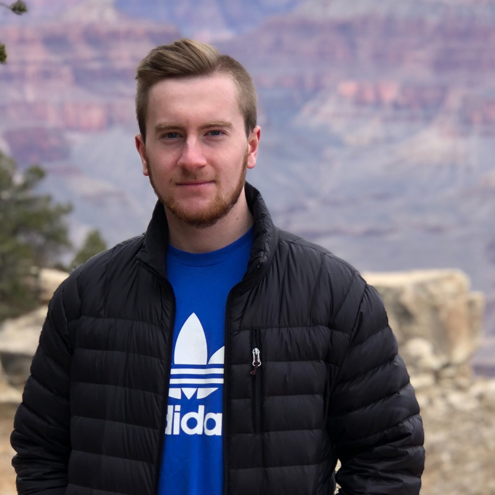 Picture of Jason Wootten wearing a blue t-shirt and a black jacket