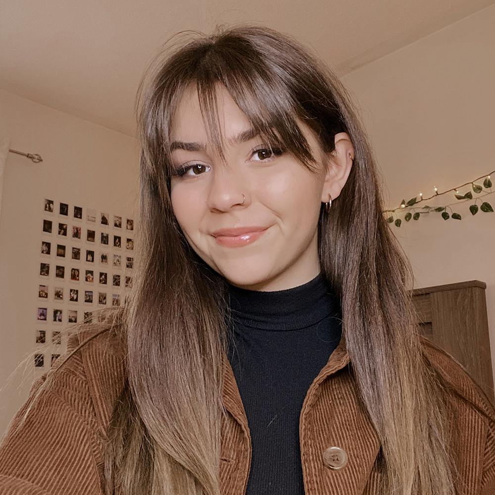 Picture of Jessica, wearing a honey-brown jacket with a turtle neck black shirt