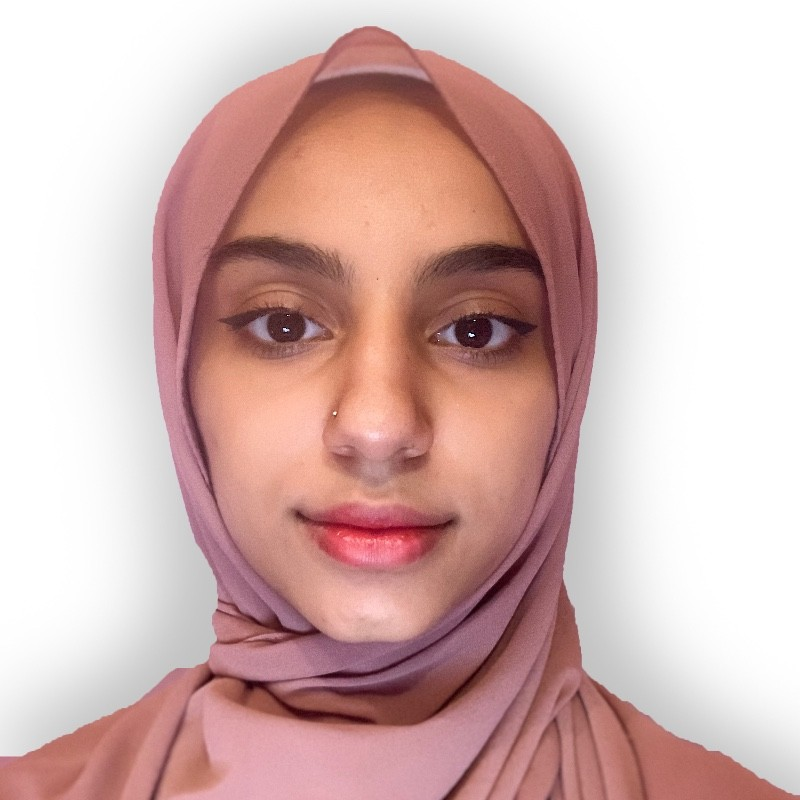 Picture of Maymona posing to the camera against a white wall wearing a salmon pink hijab