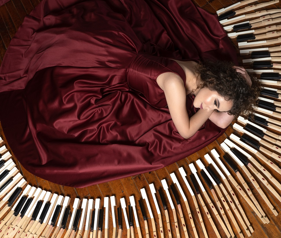 A picture of Alex Whorms in a flowing burgundy dress, surrounded by piano keys