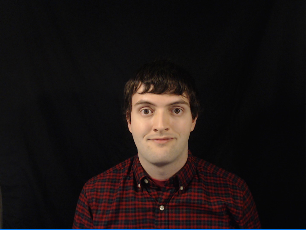 A picture of Chris Wilkinson wearing a red plaid shirt, against a black backdrop