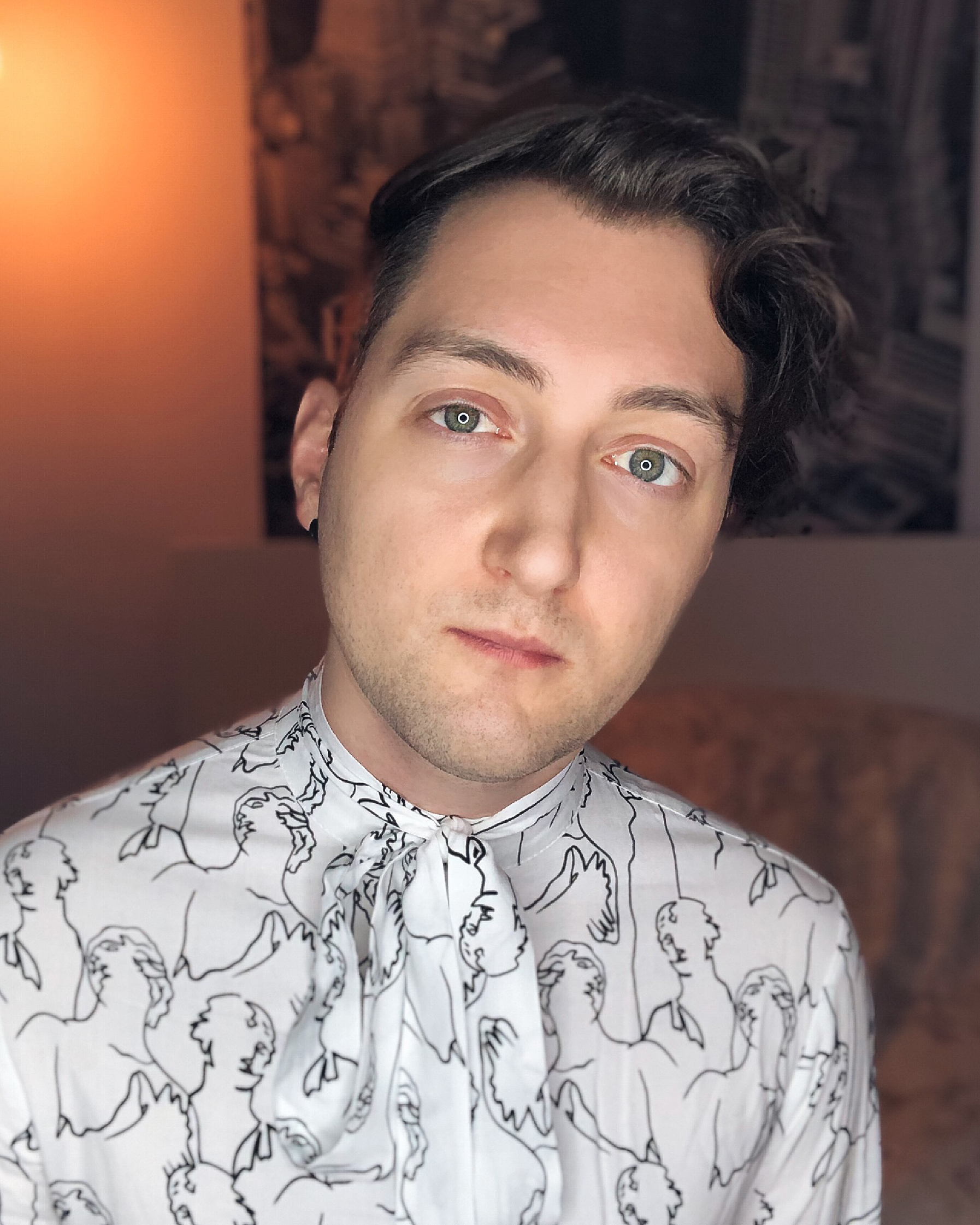 A picture of James Aries looking pensive, wearing a white/black patterned shirt