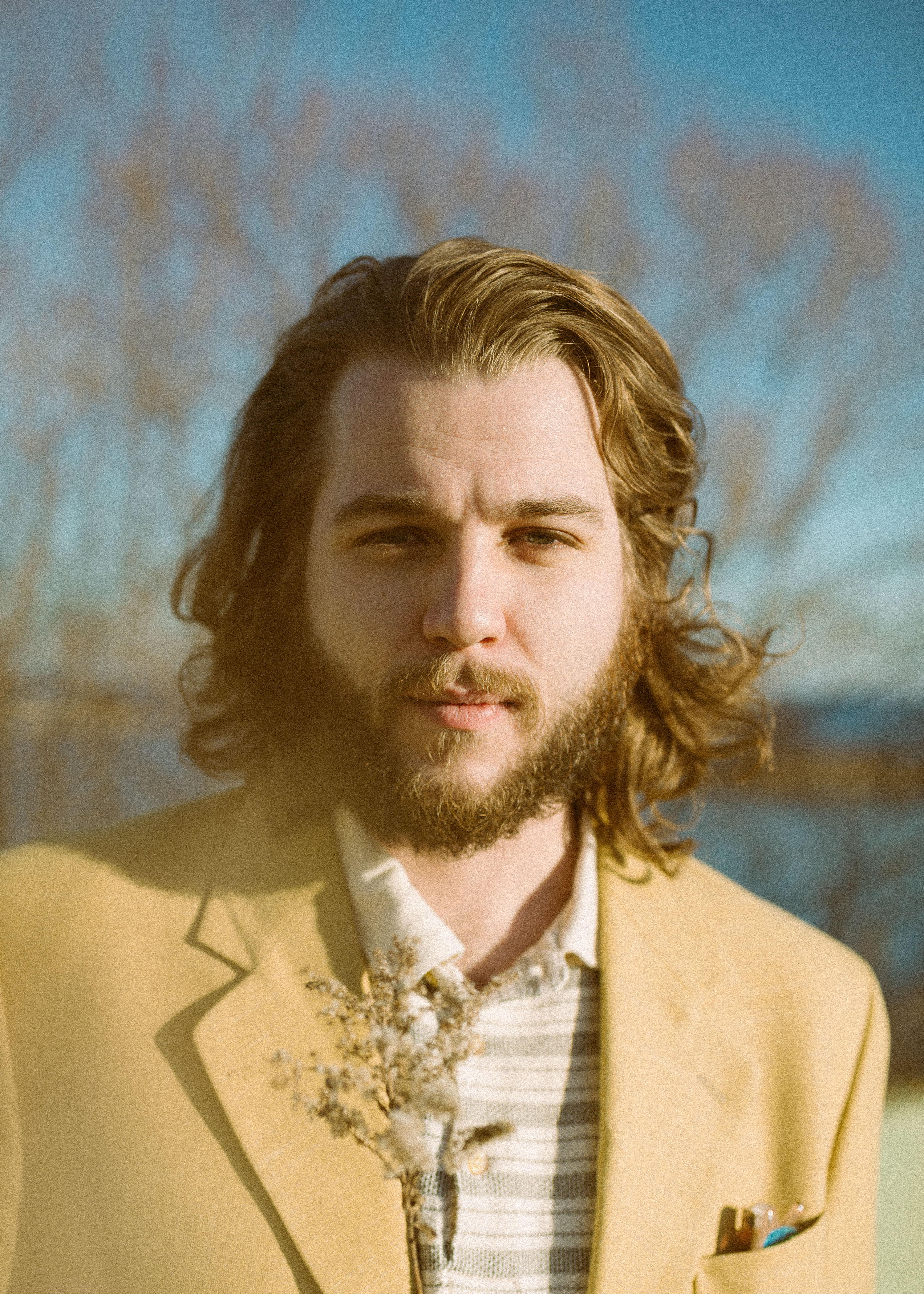 A picture of Nate Bain wearing a yellow/beige jacket, in an outdoor environment